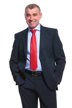 mid aged business man smiling for the camera while holding both hands in his pockets. isolated on a white