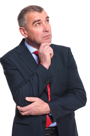 looking away from camera: pensive middle aged business man looking away from camera while holding his hand at his chin. isolated on a white  Stock Photo