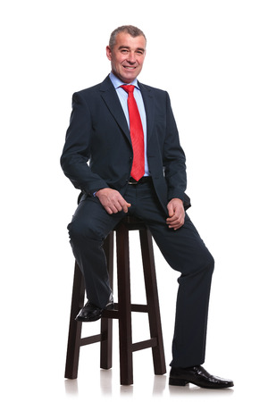business for the middle: portrait of a middle aged business man sitting on a high stool and smiling for the camera. isolated on a white