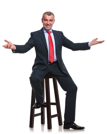 high chair: mid aged business man sitting on a high stool and welcoming you with his arms wide open and a smile on his face. isolated on a white