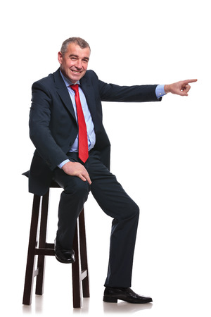 mid aged business man sitting on a high stool and pointing to his side while smiling for the camera. isolated on a white