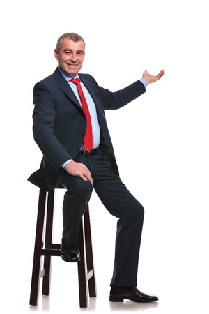 stool: seated mid aged business man presenting something in the back and smiling for the camera. isolated on a white