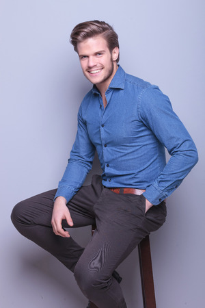 hand in pocket: happy young elegant casual man smiling to the camera while sitting on a high chair
