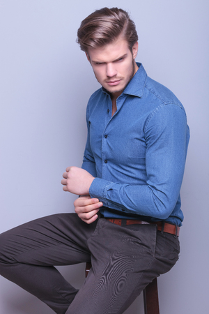 elegant fashion young man sitting , fixing his sleeve and looking away on gray background photo