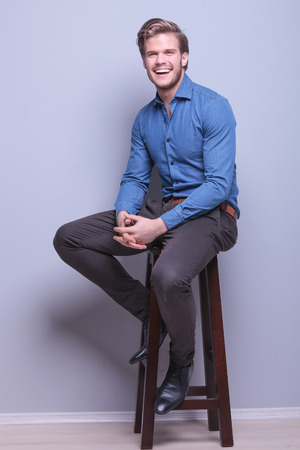side pose: laughing young casual man sitting on a high chair in studio