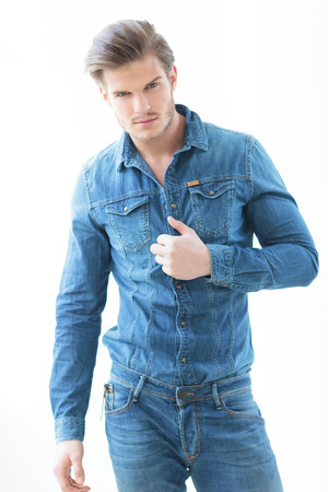 sexy man in jeans casual clothes holding his shirt and smile to the camera photo
