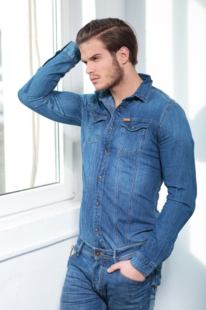 man with long hair: fashion man in jeans clothes with hand on his head looking outside the window