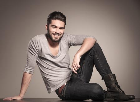 Gelukkig jonge man zit op de vloer en glimlacht naar de camera