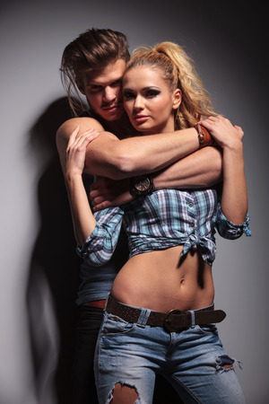 muscular woman: man and woman standing embraced close to each other in studio Stock Photo