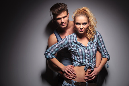 sexy young couple looking happy and smile to the camera in studio photo