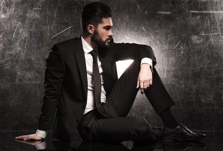 zijkant van een elegante business man in zwart pak en stropdas op zoek weg