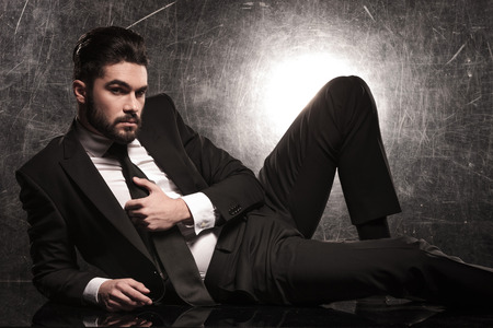 lie down: sexy bearded business man holding his tie while lying on the floor
