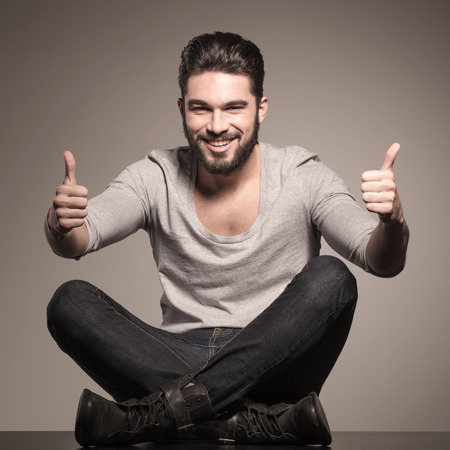sit up: happy young casual man sits and make the ok thumbs up hand sign