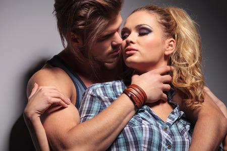 sexy muscular man embracing his girlfriend in studio photo