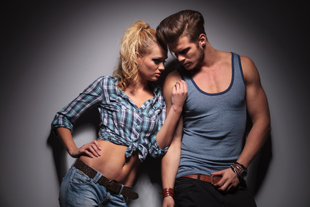 passionate couple standing against gray studio wall, in a hot pose photo