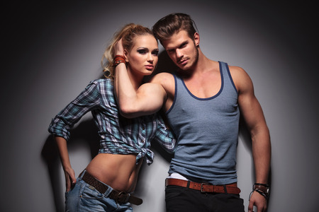 muscular man holding his girlfriend close, both looking at the camera photo