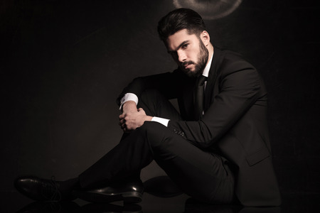 full suit: dramatic picture of a sexy young business man sitting on the floor Stock Photo