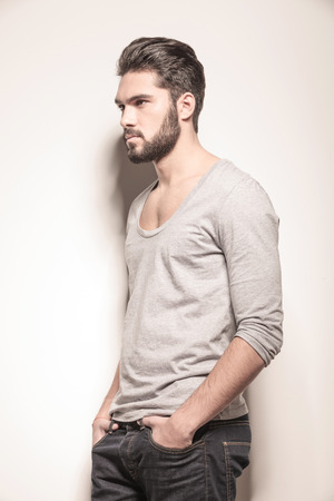 poses de modelos: vista lateral de un joven atractiva con las manos en los bolsillos en el estudio