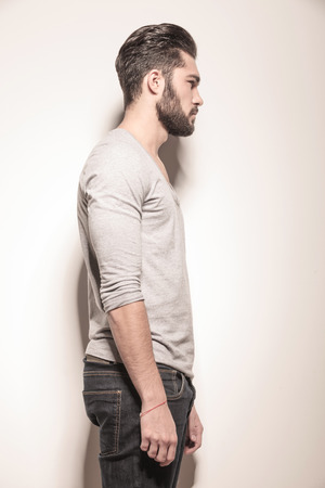 men hairstyle: polaroid side portrait of a young man with beard in studio