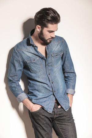 hombre con barba: vista lateral de un hombre ocasional triste mirando hacia abajo, fotografía de estudio