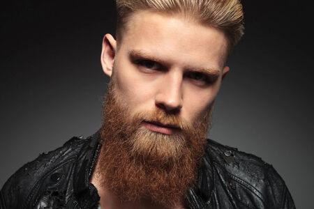 hombre con barba: Primer plano de un hombre joven ocasional con una barba inconformista, mirando a la cámara. sobre un fondo oscuro del estudio Foto de archivo