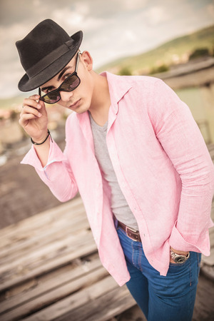young fashion casual man with hat holding his sunglasses and looks to the camera photo