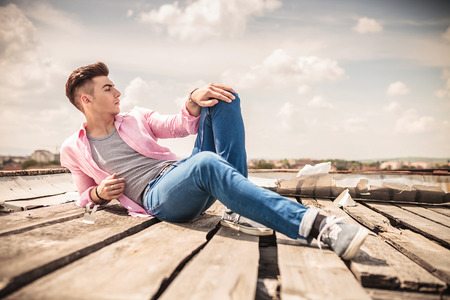 sit down: modelo posando mientras se está acostado y mira hacia otro lado Foto de archivo