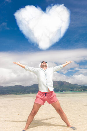 happy young man with hands in the air celebrating love on the beach, heart shaped cloud above him photo