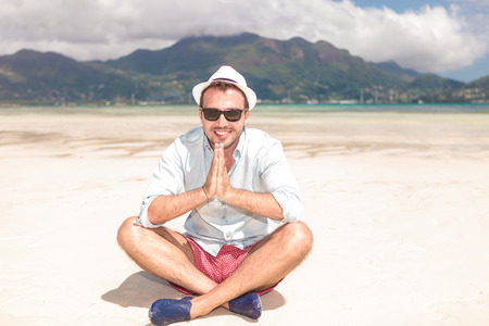 smile please: young man sits on the beach and prays for more sun in his vacation