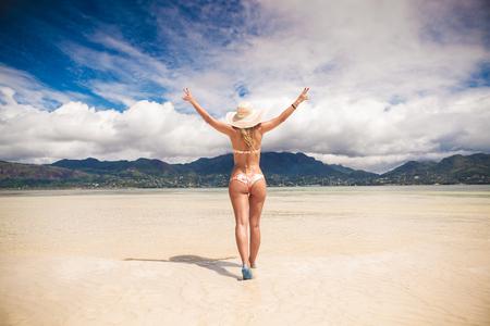 nue plage: sexy jeune femme blonde marchant avec ses mains en l'air sur une belle plage des Seychelles Banque d'images