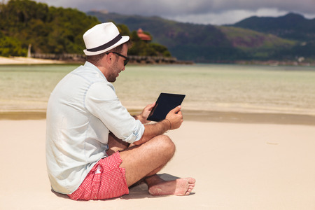 young casual man sitting on the beach and reading on his touchscreen tablet