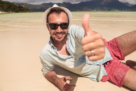 happy young man with hat and sunglasses lying down on the beach of seychelles and makes the ok thumbs up hand sign photo