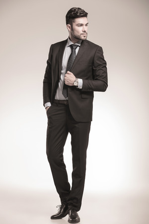 cool business man looking to his side , full body picture in studio photo