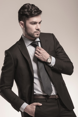 side view of a young business man fixing his tie in studio photo