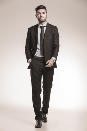 young business man walking forward with one hand in his pocket, studio picture photo