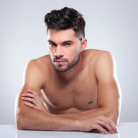 nackter junge: sitzen nackte Mann mit gekreuzten H�nden in die Kamera blicken Lizenzfreie Bilder