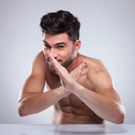 homme nu: homme nu assis et posant dans une position de d�fense de karat�, rigoler Banque d'images