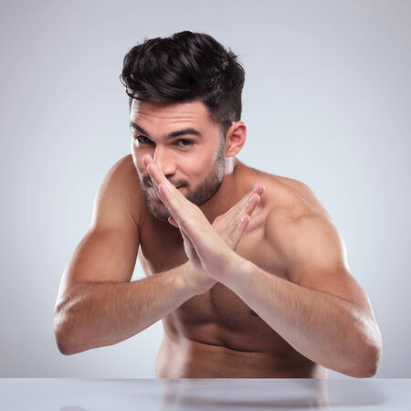 naked man: naked man sitting and posing in a karate defence position, fooling around Stock Photo