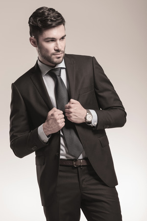 sexy young business man holding his collar and looks away to his side photo