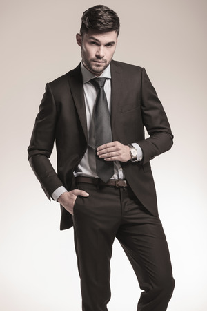 sexy young business man holding his tie and looking at the camera photo