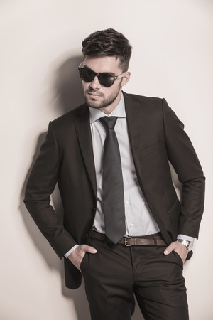 elegant fashion model in suit and tie looking cool with his sunglasses on Stock Photo