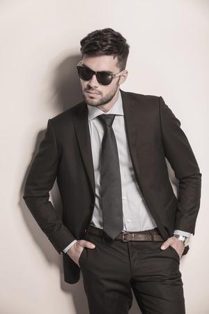 modelo de moda elegante en traje y corbata que parece fresca con sus gafas de sol en
