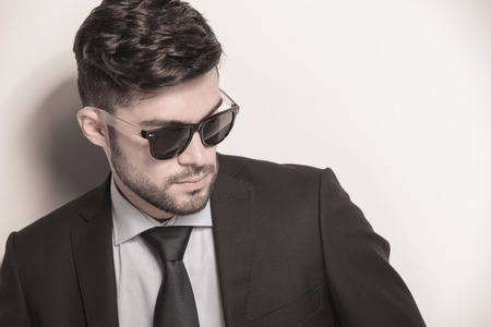 side closeup picture of a sexy young business man wearing sunglasses and looking away photo