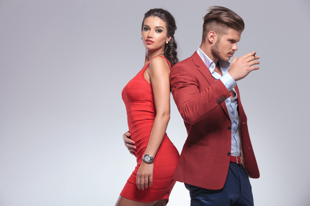 fashion young couple posing, man with cigarette in hand and woma looking at the camera photo