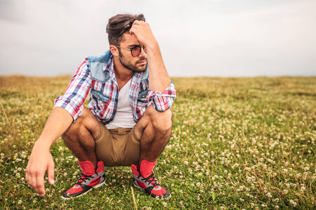 crouched: crouched casual man in a grass field thinking and looking away to his side Stock Photo