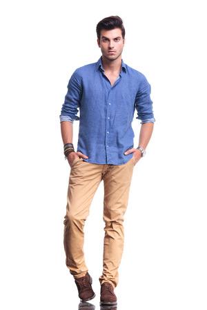 foto de cuerpo entero de un joven casual con las manos en los bolsillos sobre fondo blanco