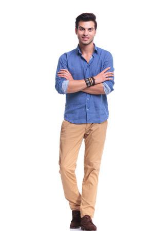 mani incrociate: quadro completo del corpo di un giovane uomo casual con le mani incrociate sorridente su sfondo bianco