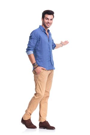 cuerpo entero: hombre feliz ocasional que presenta algo en el fondo blanco, foto de cuerpo entero
