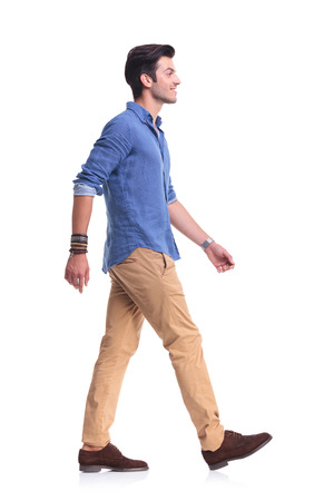 side view of a smiling young casual man walking , on white background