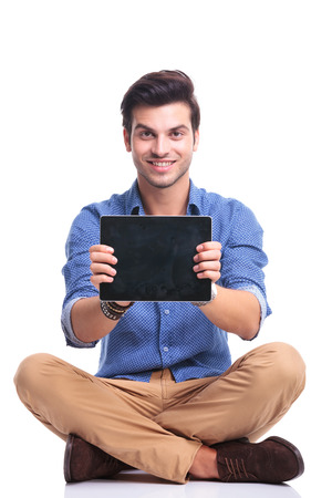 young smiling seated man showing the screen of his tablet pad computer on white background photo